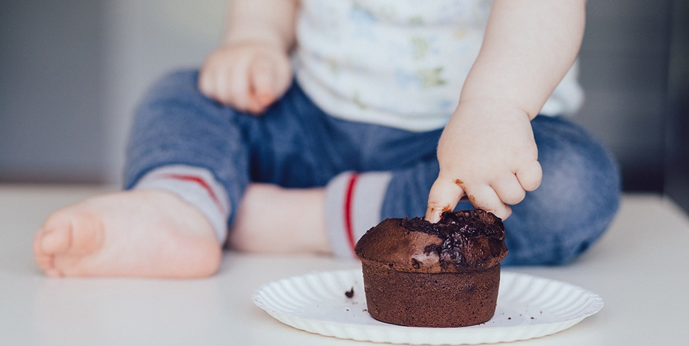 main de bébé dans du gateau au chocolat